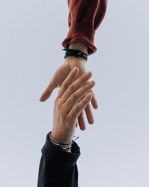Image of two white hands reaching out and nearly touching each other.
