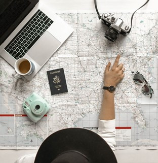 Image of a large open map with various travel items placed on top of it including a passport, a professional camera, sunglasses, a laptop and an instant print camera. A person that is mostly out of the shot points to a city or town on the map using their right index finger. They are wearing a large wide-brimmed hat, a white long-sleeved t-shirt and a black watch.