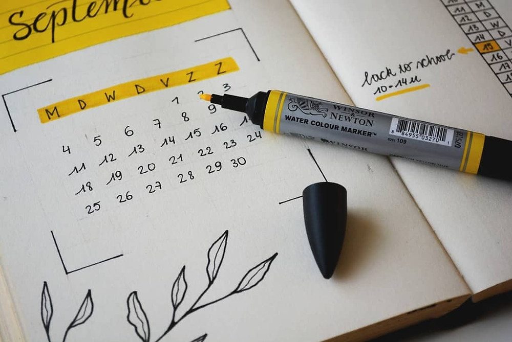 Picture of an open yellow highlighter with its cap sitting on an open calendar diary, the month of September is visible in the picture.