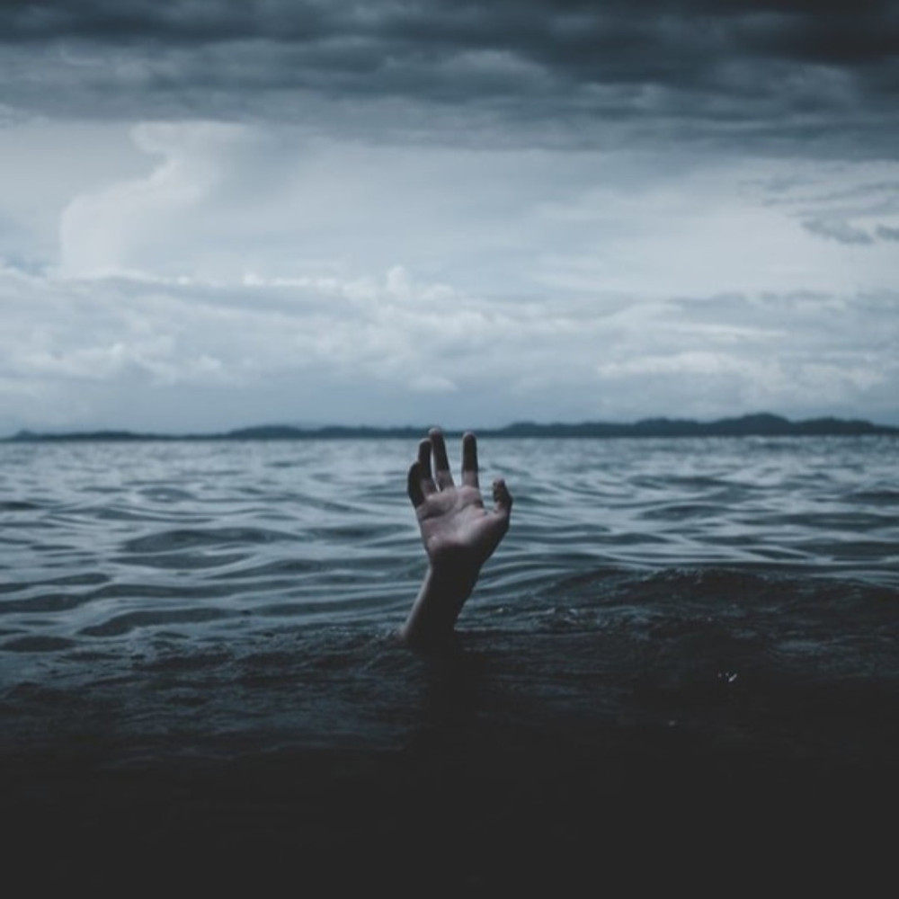 Image of a vast body of water pictured on a stormy day. There is a hand stretching out of the water.