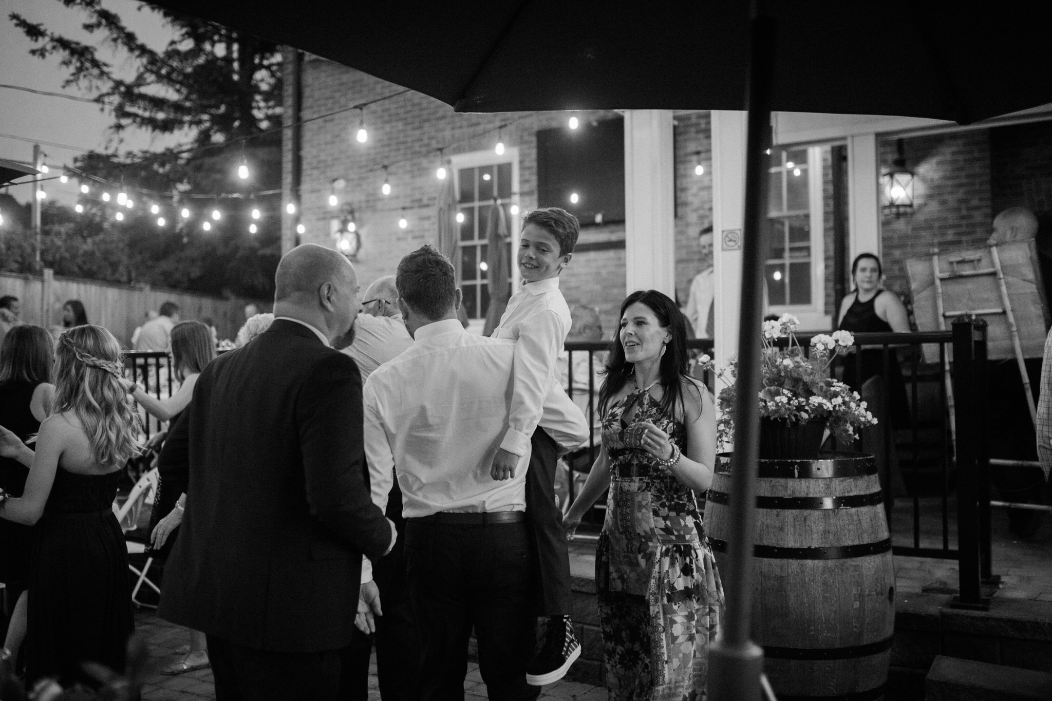 Harvest Restaurant Wedding Brooklin Ontario - Father carrying son under string lights on patio