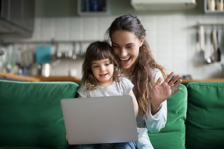 Happy mother and kid daughter waving hands looking at web camera using laptop for video ca