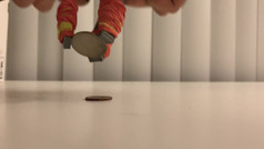 The hand picking up a quarter from a flat table