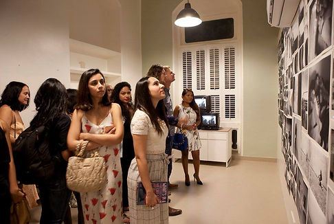 A small crowd gathered at an evening photograhy exhibition