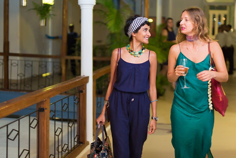 Two women walking down the courtyard in evening dresses with champagne