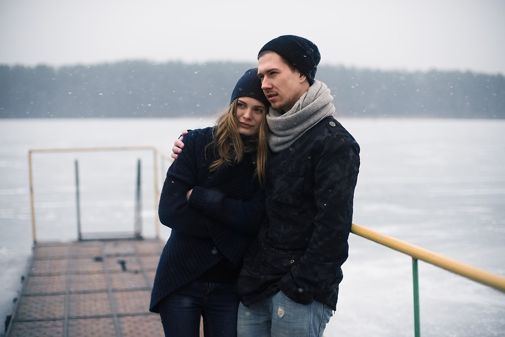 couple hugging serious sad cold weather