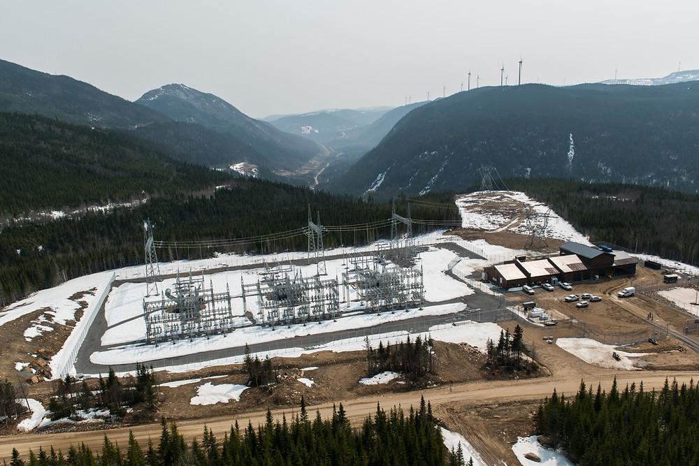 Des bâtiments et des installations de transformation électrique dans un paysage en montagne.