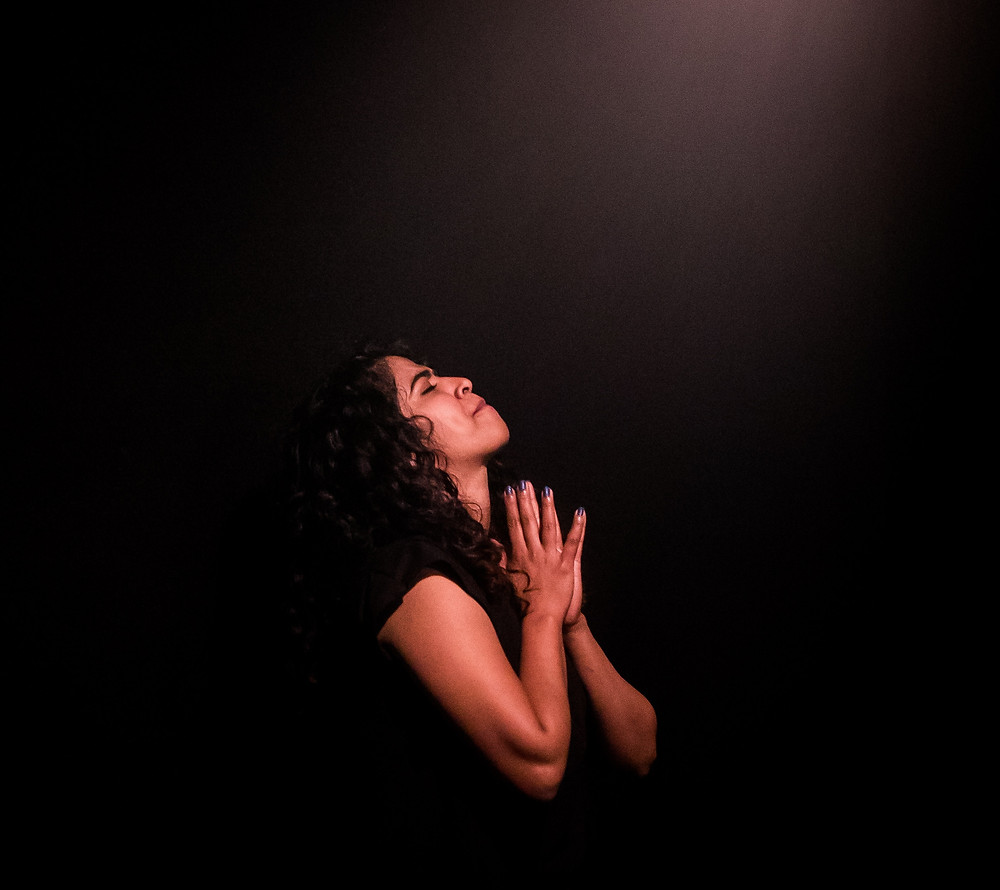 Woman praying in a dark room