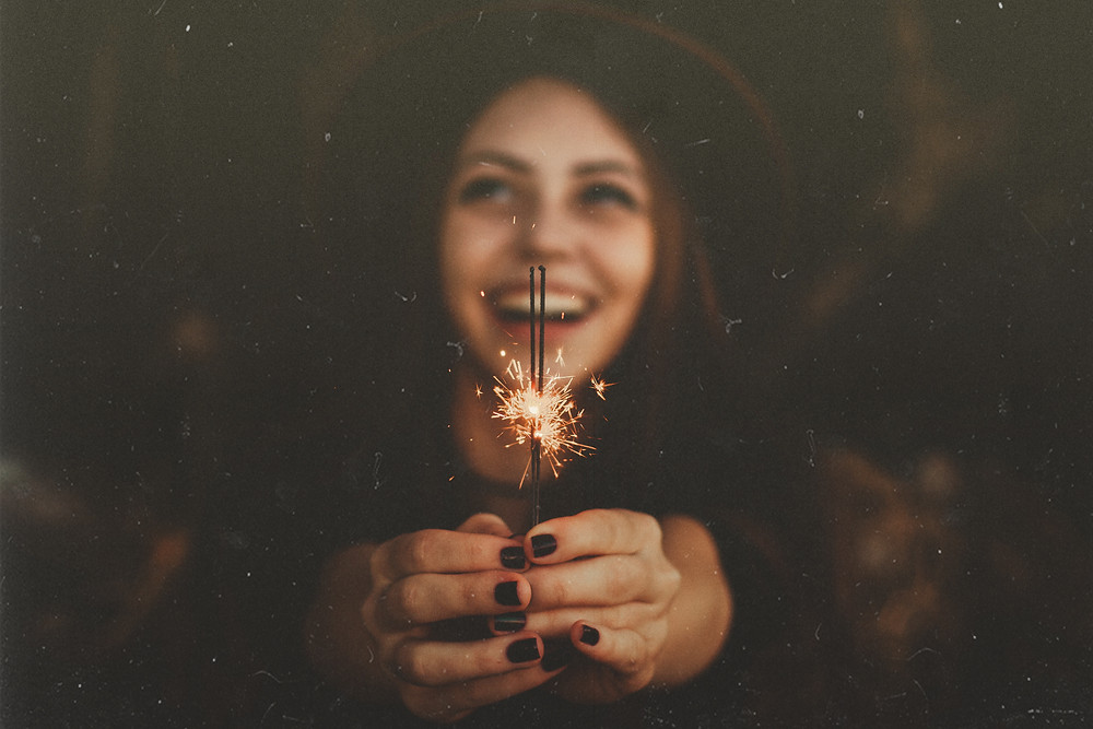 Lady with hat on holding a sparkler