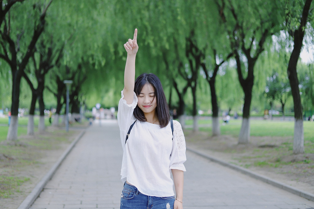 Asian Woman standing with right arm in the air with her finger pointing up