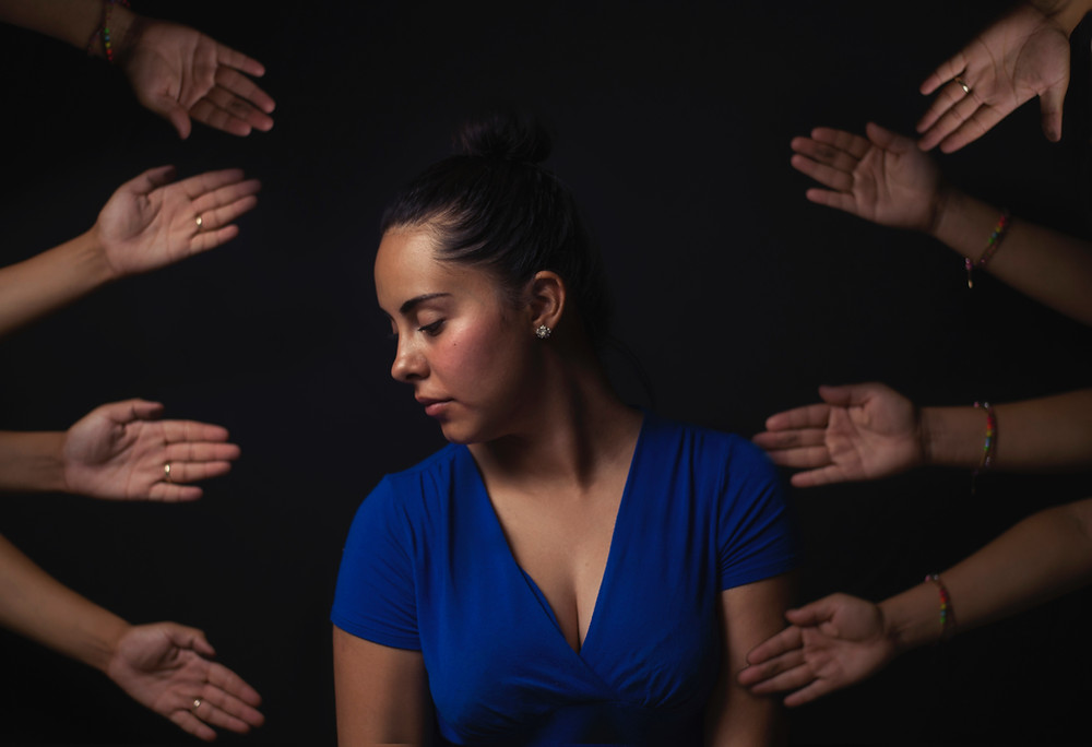Woman in blue shirt surrounded by hands
