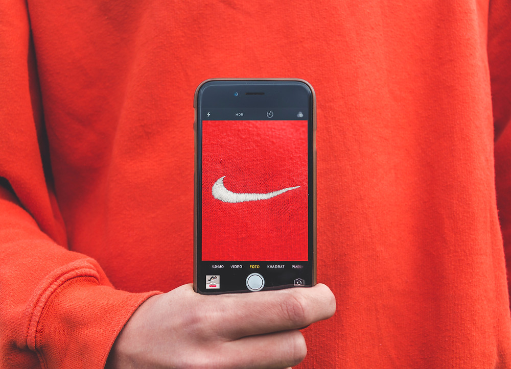 Guy in a Red Nike Sweatshirt holding his phone in front of the sweatshirt