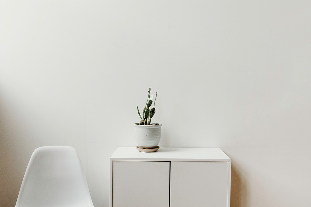 All White Room with Cabinet Table, Chair and Green Plant in a white Pot