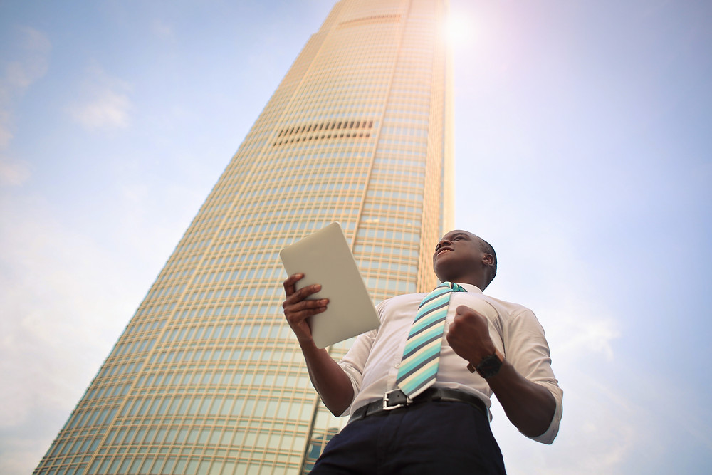 Black Man Standing in Front of Skyscraper with tablet in his hand