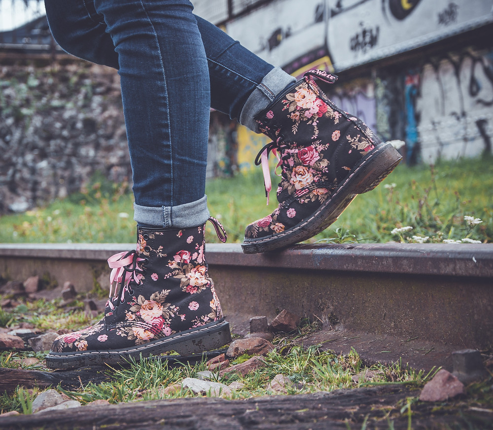 Floral boots stepping off a railroad track