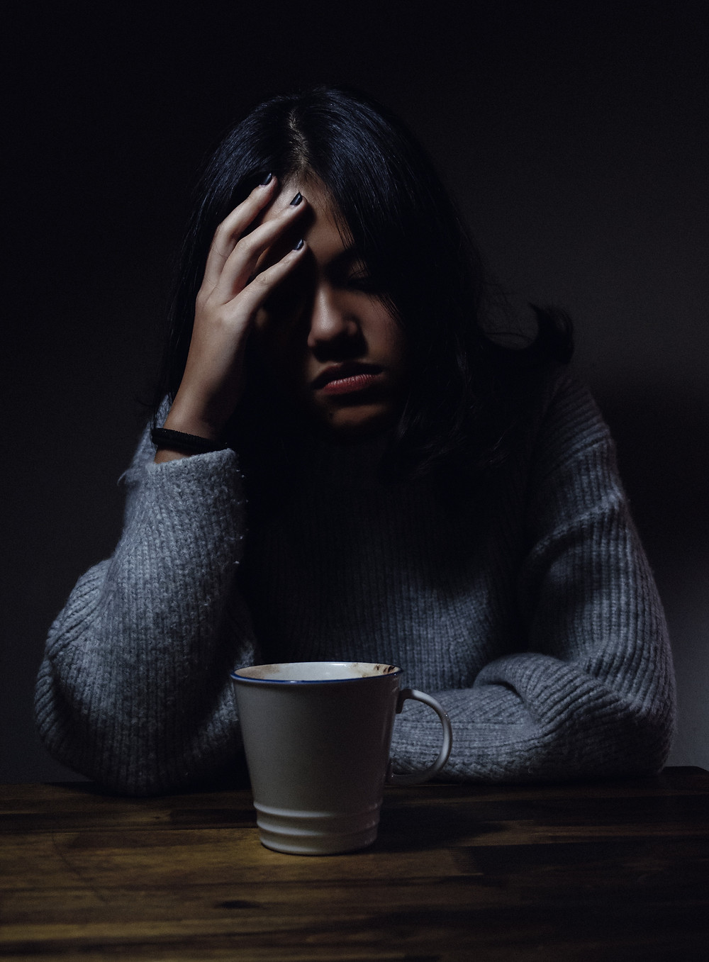 Woman sad with her hand on her head sitting on table with coffee cup