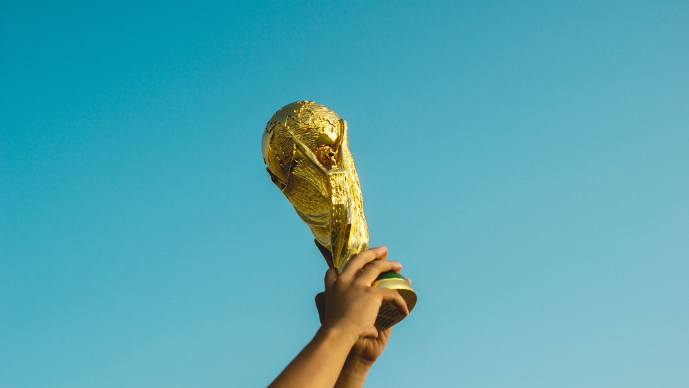 Person holding gold trophy in the air