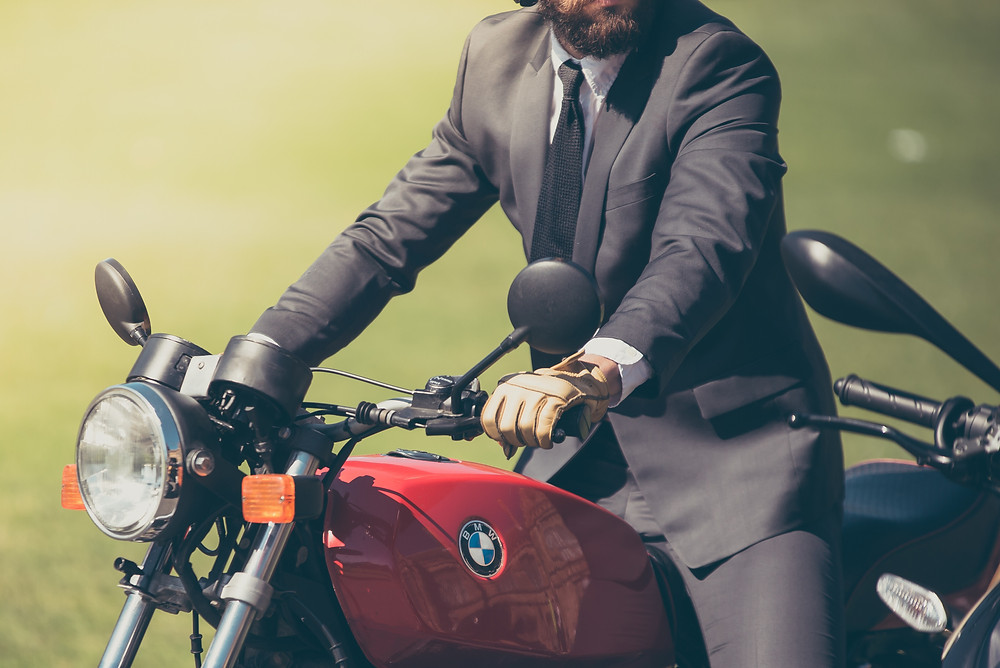 Guy in a suit on a red motorcycle