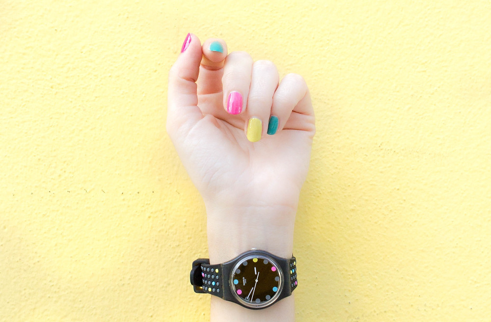 White Woman Hand with Watch on behind a Yellow Wall