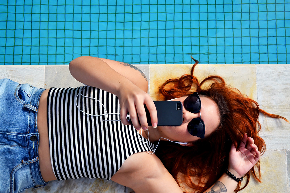 Girl laying by the pool in a black and white stripe tank top with sunglasses on taking a selfie