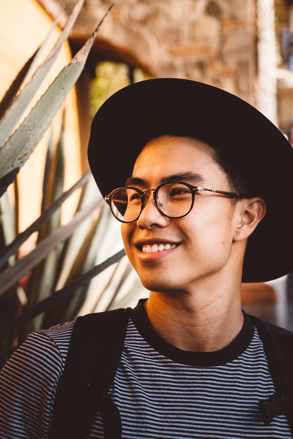 Asian Man with hat and glasses on smiling