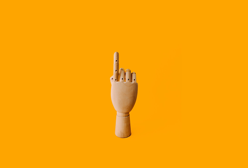 Yellow Background with Mannequin Hand with Pointer Finger pointing up