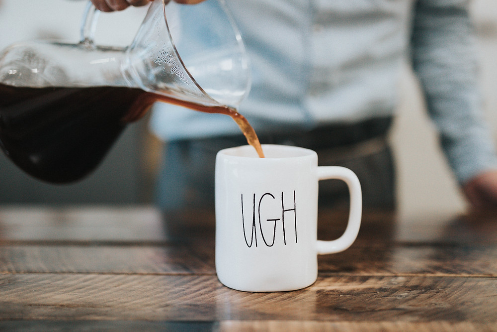 Pouring Coffee in a coffe mug with the word Ugh on it