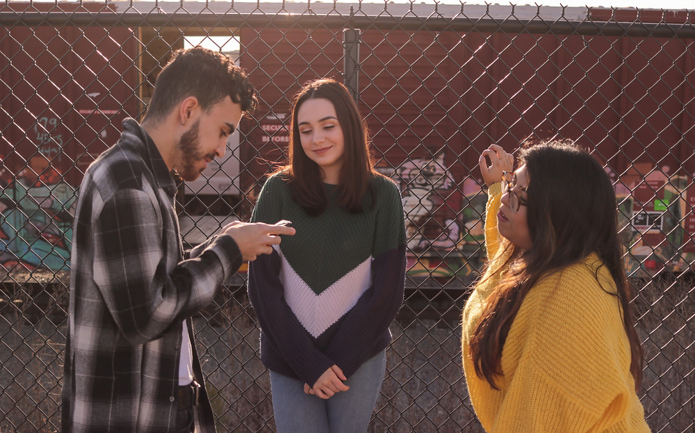 Three teenagers on a fired fence talking