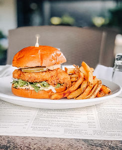 Fried chicken sandwich with pickles, harissa aioli and french fries