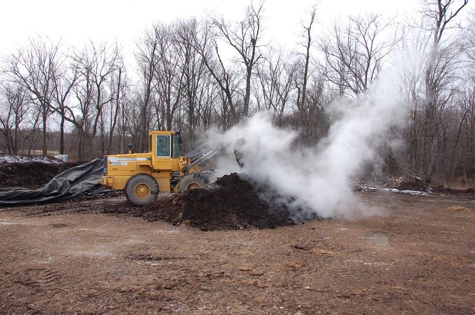 Compost being turned.  The core temp reaches 160°, making it safe to compost all meat scraps.
