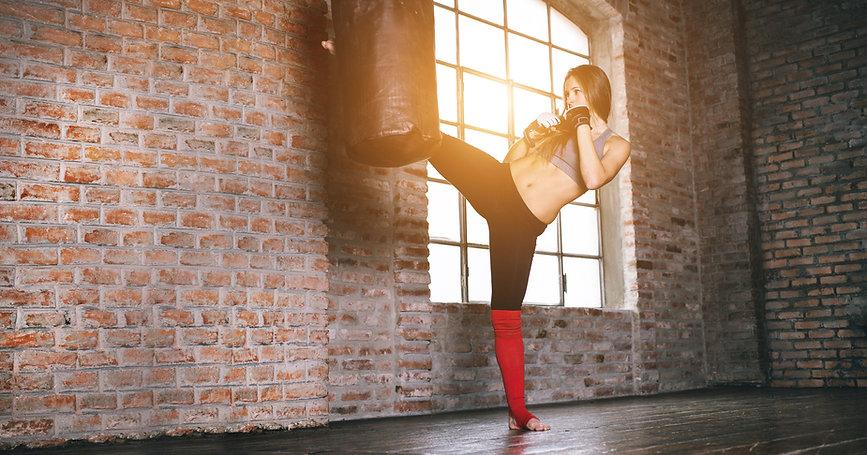 Nainen potkaisee nyrkkeilysäkkiä tehdasmaisessa rakennuksessa punaista tiiltä on ympärillä.