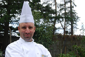 In Chef attire with white tall (toque) hat