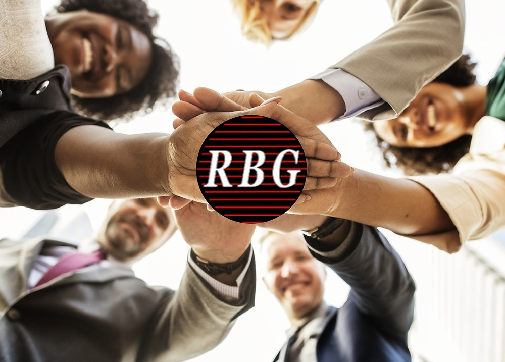 Team of smiling people with hands on the RBG Janitorial logo