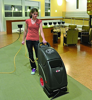 Woman operating carpet extractor