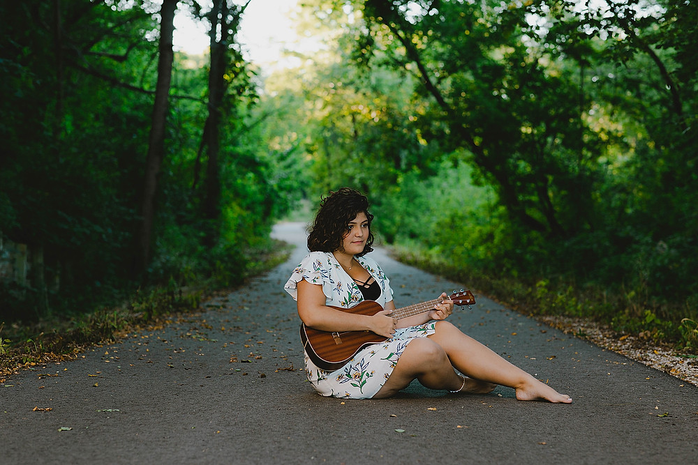 senior girl sitting on ground with ukulele