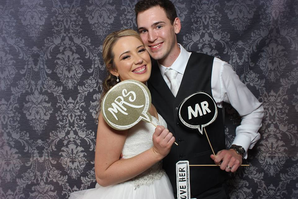 A happy couple with some DIY photo booth props.
