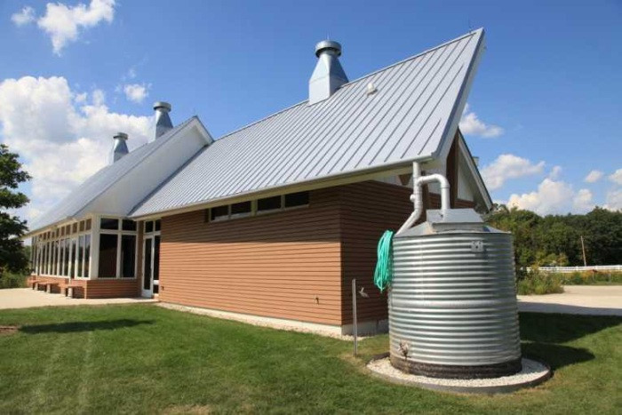 Brown and silver house with external rainwater capture tank