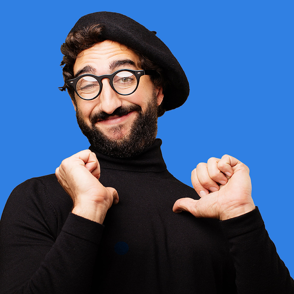 Smiling artsy man wearing a beret connecting with his inner artist and pointing to himself with a blue background.