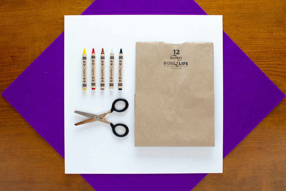 Cave Art Craft materials with scissors, paper bag, and colorful crayons