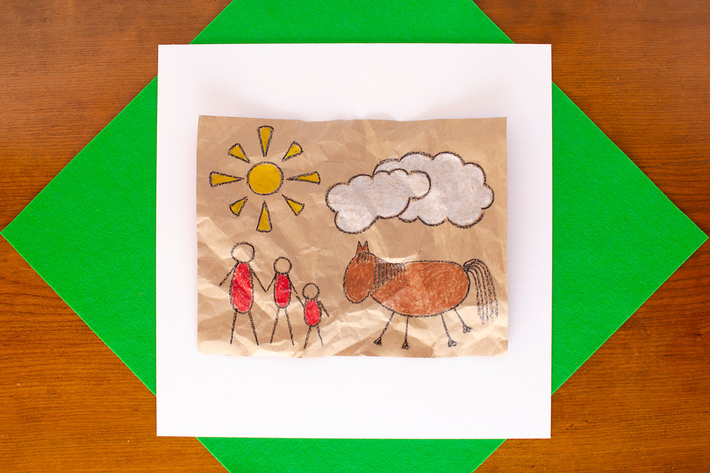finished Cave Art Craft with colorful crayon drawing of family with horse, sun, cloud on kraft paper