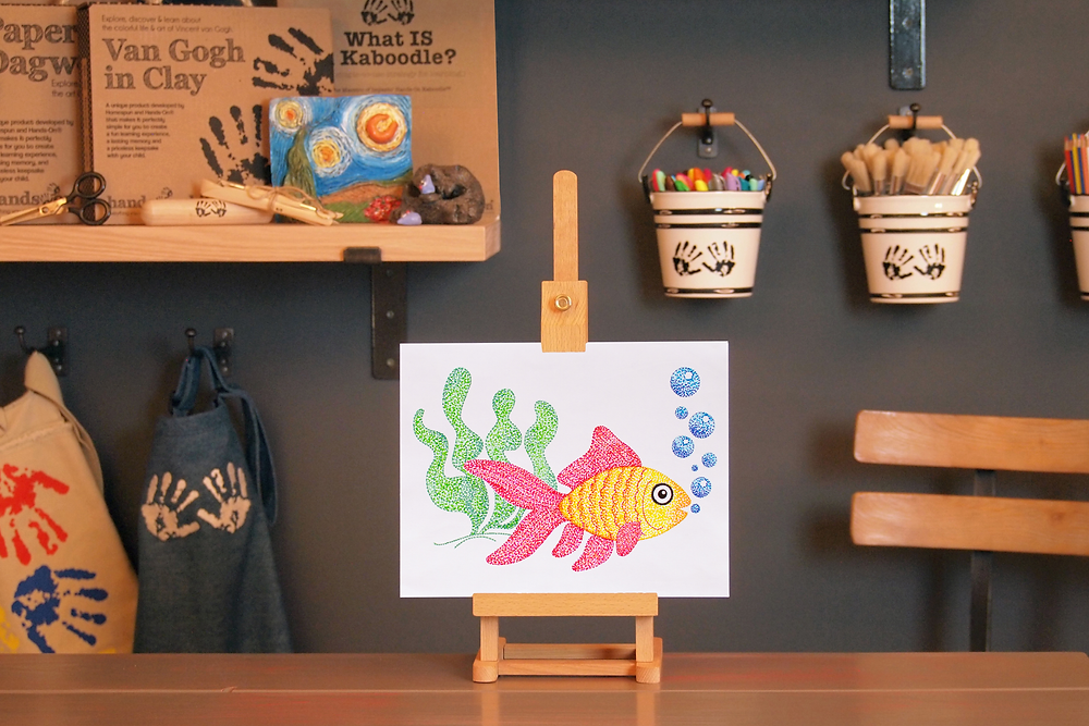 finished Pointillist Marker Art Craft of fish on an easel in the Art to Know witth MommyO vlog set