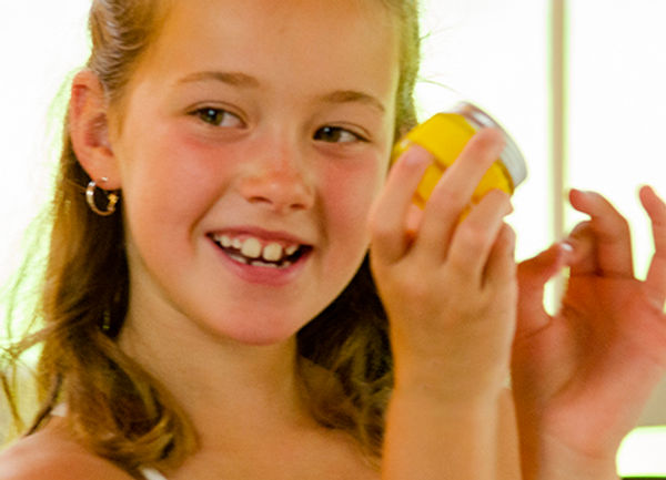 Smiling girl holding yellow pigment-rich acrylic paint in glass paint pot makes memories as she creates a unique masterpiece