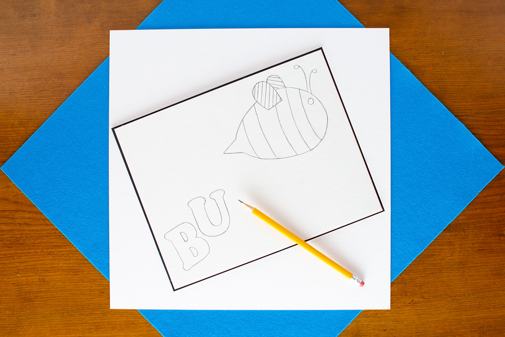 Onomatopoeia Art that Pops step 1 with a pencil sketch of a bee and the letters BU, pencil