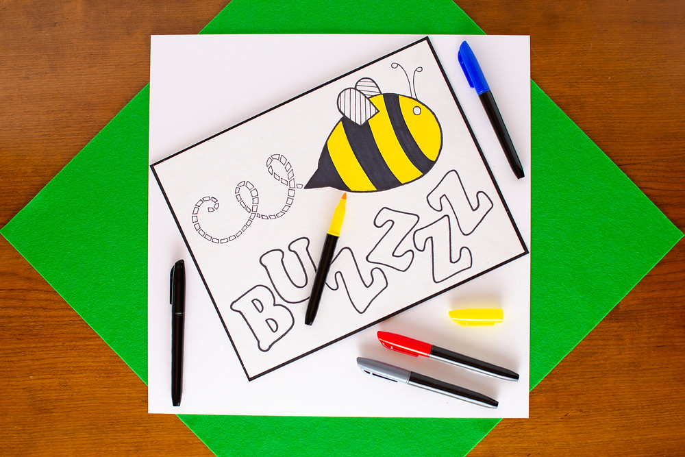 Onomatopoeia Art that Pops step 3 with partially colored bee with word buzzzz, markers in the colors yellow, red, blue, gray, black
