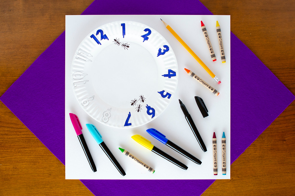 step 1 of Surreal Creature Craft with paper plate with blue clock numbers, colorful markers and crayons, and pencil