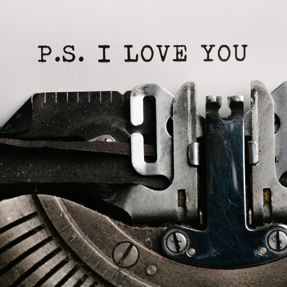 black and white close up of typewriter with creative P.S. I Love You message typewritten on paper