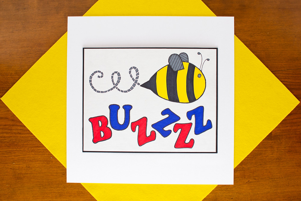 finished Onomatopoeia Art that Pops craft with a colorful bee and the word buzzzz