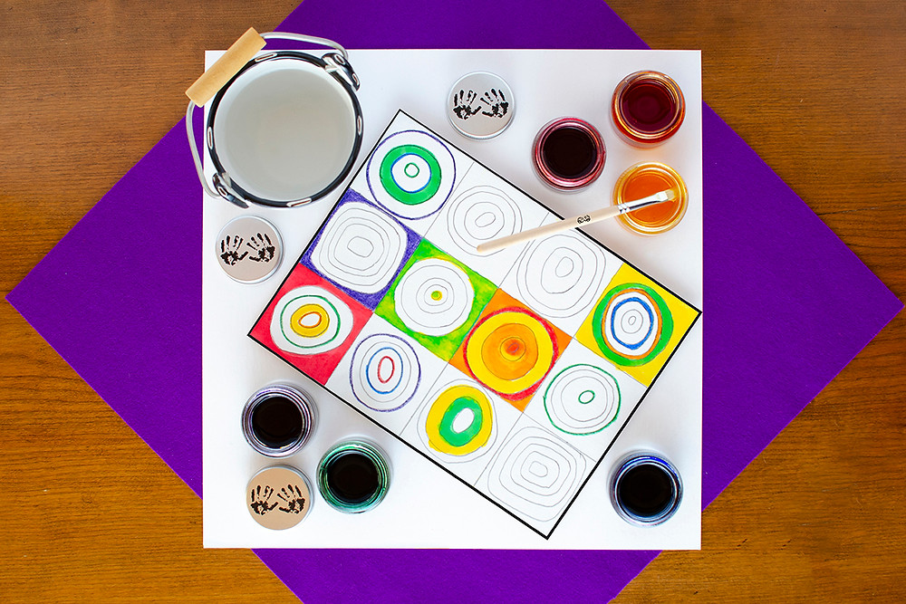 Painted Concentric Art step 3 with pencil drawing of concentric circles in squares partially painted, colorful watercolor paints, paint brush, water bucket