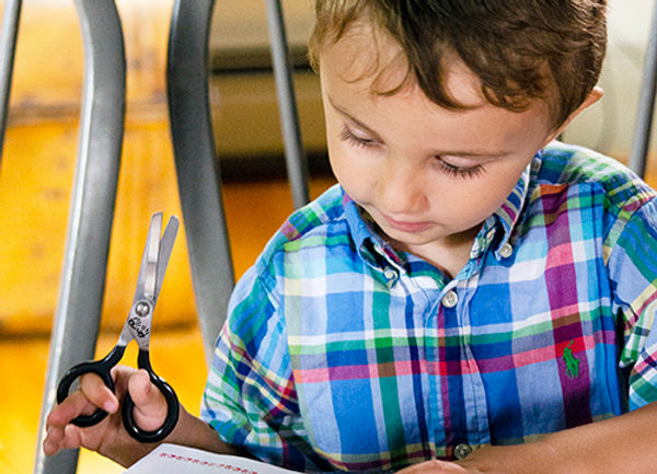 Curious boy inspired by art while thinking and reading to develop problem solving skills while holding no-slip-grip scissors