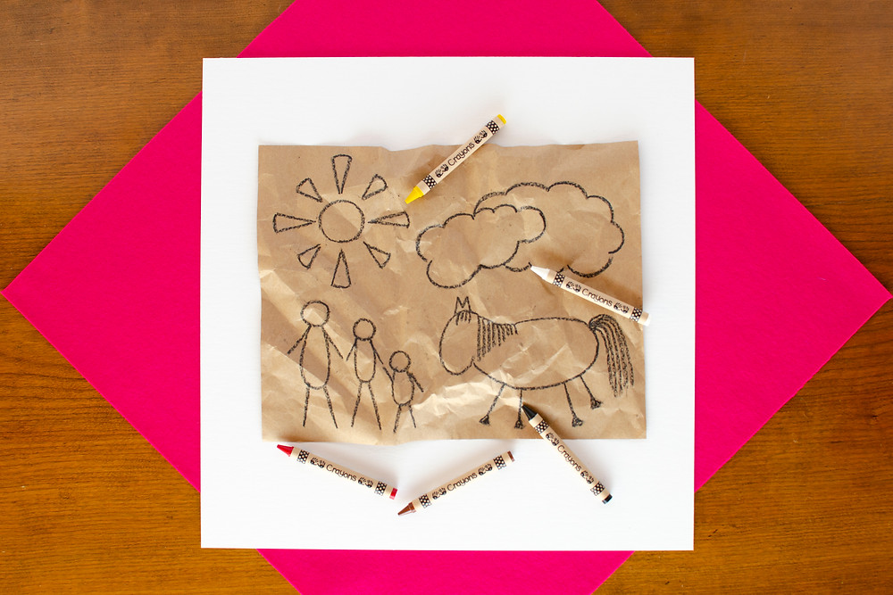Cave Art Craft step 3 with black outline drawing on crumpled kraft paper, red, brown, black, yellow, white crayons